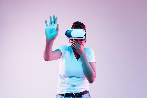 Portret van jonge afro-amerikaanse vrouw spelen in vr-bril in neonlicht op verloop achtergrond. concept van menselijke emoties, gezichtsuitdrukking, moderne gadgets en technologieën. raakt iets aan.