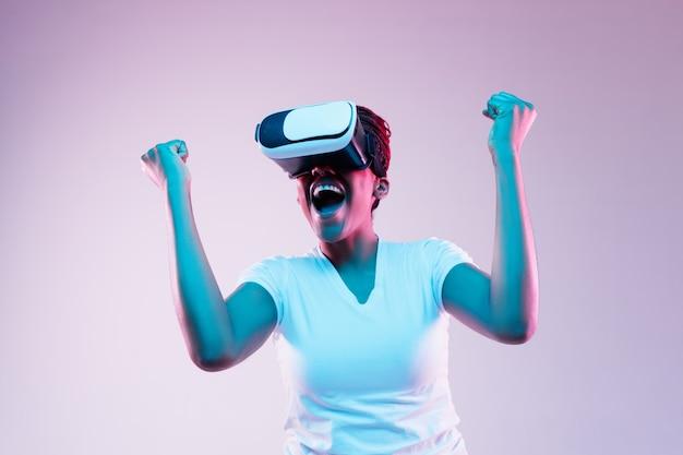 Portret van jonge afro-amerikaanse vrouw spelen in vr-bril in neonlicht op verloop achtergrond. concept van menselijke emoties, gezichtsuitdrukking, moderne gadgets en technologieën. ziet eruit als winnaar.