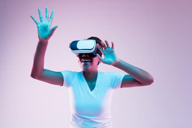 Portret van jonge afro-amerikaanse vrouw spelen in vr-bril in neonlicht op verloop achtergrond