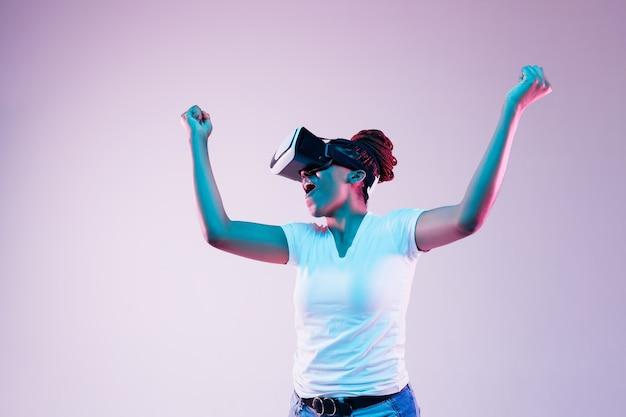 Portret van jonge afro-amerikaanse vrouw spelen in vr-bril in neonlicht op verloop.