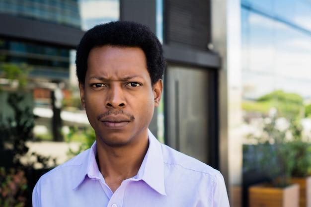 Portret van jonge afro-amerikaanse zakenman die zich buiten op straat bevindt. bedrijfsconcept.