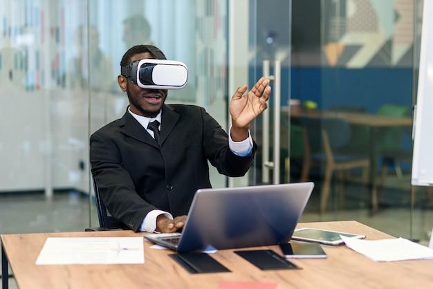 Portret van jonge afro-amerikaanse zwarte mannelijke professional met behulp van augmented reality holografische hololens in moderne kantoren