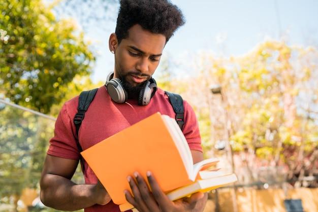 Portret van jonge afro universitaire student die en met zijn boek op de campus leest studeert. onderwijs en levensstijl concept.