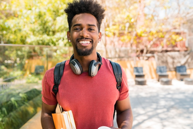 Portret van jonge afro universitaire student die zijn boeken houdt