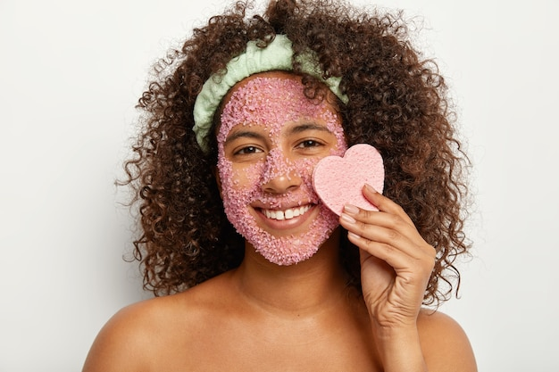 Portret van jonge afro vrouwelijke model houdt hartvormige spons in de buurt van gezicht bedekt met zoutkorrels, glimlacht breed, heeft witte tanden met kleine opening, staat naakt, drukt positieve emoties uit
