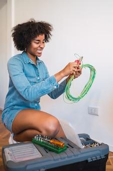 Portret van jonge afrovrouw die elektriciteitsprobleem met kabels in nieuw huis bevestigt. reparatie en renovatie huisconcept.