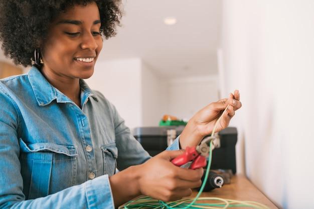 Portret van jonge afrovrouw die elektriciteitsprobleem met kabels in nieuw huis bevestigt