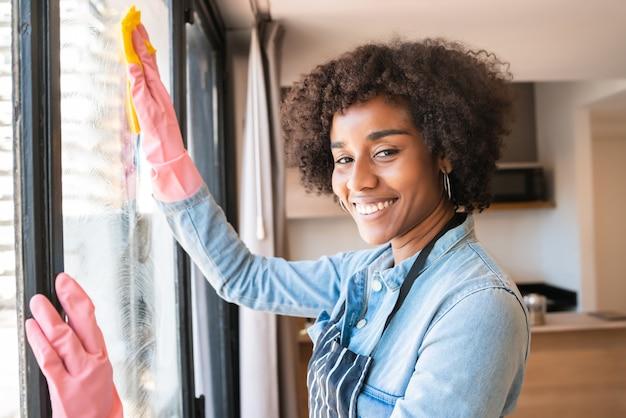 Portret van jonge afrovrouw in handschoenen die venster met lap thuis schoonmaken. huishoudelijk werk, huishouding en schoonmaakconcept.