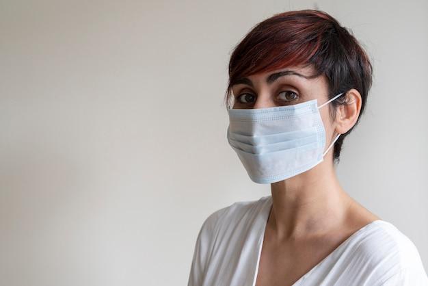 Portret van jonge arts die een beschikbaar gezichtsmasker draagt dat mogelijke kiemen in mond behandelt. voorkom besmettelijke virale ziekten zoals corona virus covid 19. stop de voortplanting en gebruik voorzichtigheidsmaatregelen.
