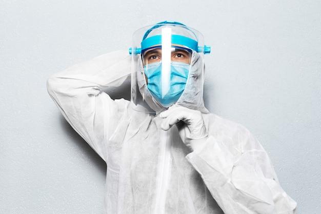 Portret van jonge arts die ppe-pak draagt tegen coronavirus en covid-19, op achtergrond van grijze muur.
