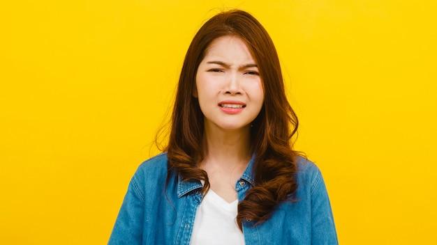 Portret van jonge aziatische dame met negatieve expressie, opgewonden schreeuwen, emotionele boos huilen in casual kleding en kijken naar de camera over gele muur. gelaatsuitdrukking concept.