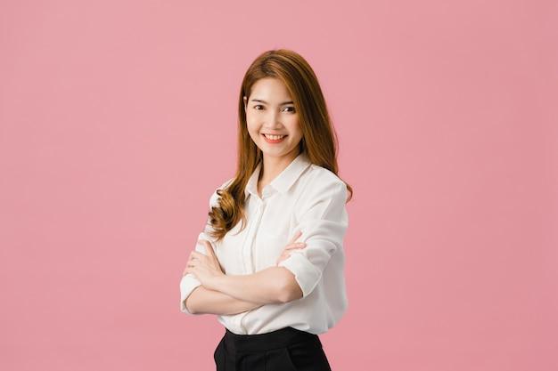 Portret van jonge aziatische dame met positieve uitdrukking, armen gekruist, breed glimlachen, gekleed in casual kleding en camera kijken over roze achtergrond.