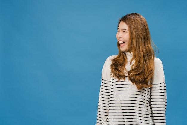 Portret van jonge aziatische dame met positieve uitdrukking, breed glimlachen, gekleed in vrijetijdskleding over blauwe muur