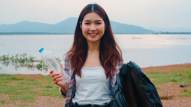 Portret van jonge aziatische dame vrijwilligers helpen de natuur schoon te houden met plastic flessenafval en zwarte vuilniszakken op het strand. concept over milieuvervuiling problemen.
