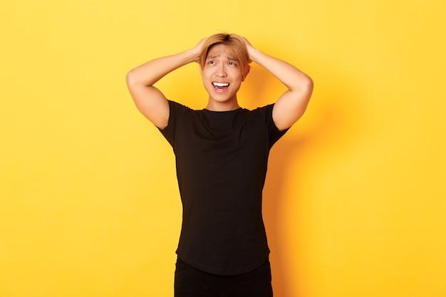 Portret van jonge aziatische kerel die in paniek raakt, angstig en boos kijkt, handen op het hoofd houdt en grimassen trekt, zich over gele muur bevindt