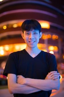 Portret van jonge aziatische man buiten 's nachts met gekruiste armen