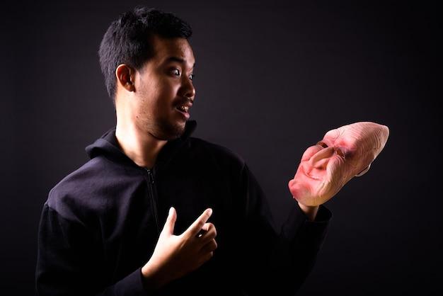 Portret van jonge aziatische man met hoodie en horror masker op zwart