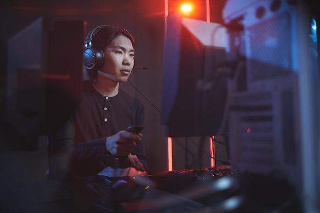 Portret van jonge aziatische man spelen van videogames met behulp van race-shift in donkere cyber interieur, kopie ruimte