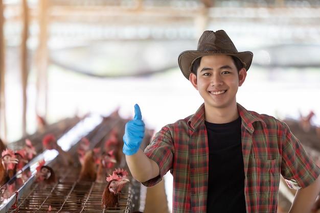Portret van jonge aziatische mensenlandbouwer in de kippenlandbouwbedrijf van eieren.