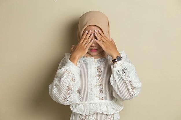 Portret van jonge aziatische moslimvrouw die hijab draagt, behandelt haar gezicht met haar handen