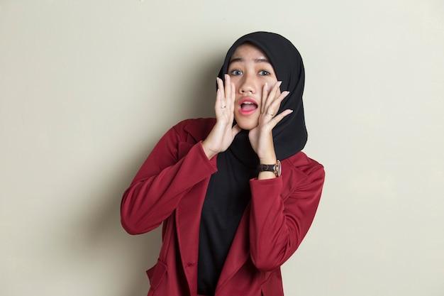 Portret van jonge aziatische moslimvrouw die hijab draagt die en schreeuwt schreeuwt