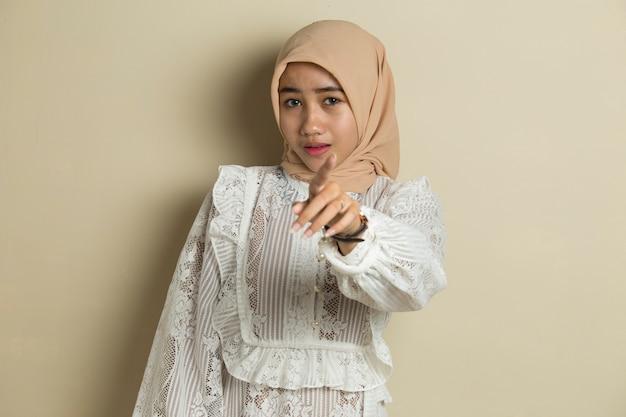 Portret van jonge aziatische moslimvrouw die hijab draagt die terwijl vooruit wijst