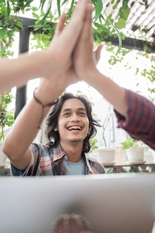 Portret van jonge aziatische studenten die in een koffie samenkomen die high five doen