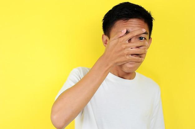 Portret van jonge aziatische tiener ongelukkig bang man, geïsoleerd op gele achtergrond