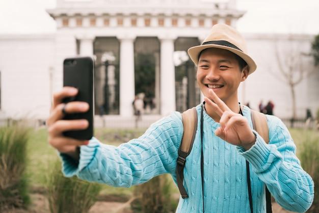 Portret van jonge aziatische toerist die een selfie met mobiele telefoon buiten in de straat neemt.