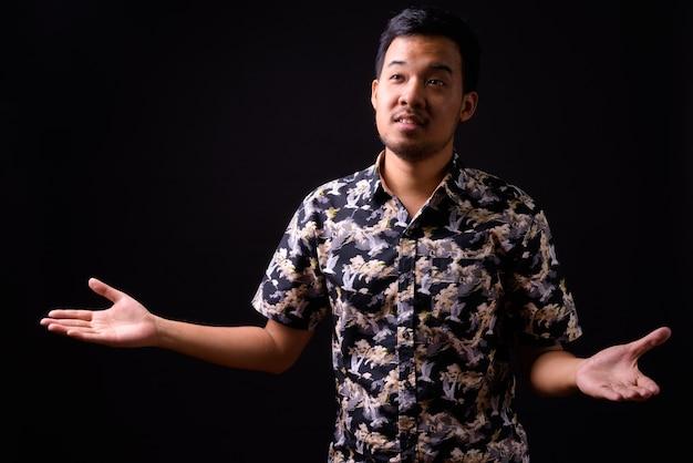 Portret van jonge aziatische toeristische man met boheemse shirt op zwart