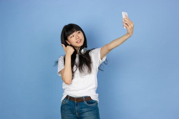 Portret van jonge aziatische vrouw dat op blauwe studioruimte wordt geïsoleerd