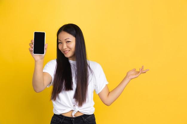 Portret van jonge aziatische vrouw dat op gele muur wordt geïsoleerd