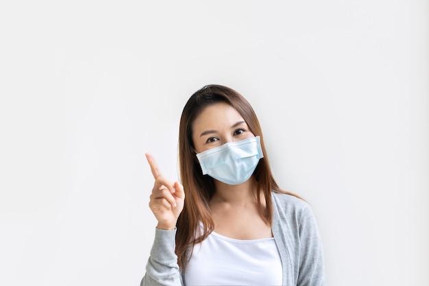 Portret van jonge aziatische vrouw die beschermend masker draagt dat met omhoog wijsvinger richt