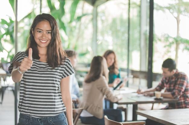 Portret van jonge aziatische vrouw die duim toont na haar groepswerk te ontmoeten