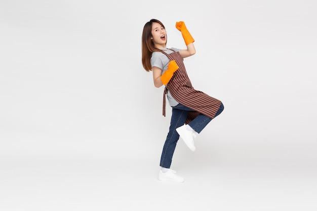 Portret van jonge aziatische vrouw die en oranje rubberhandschoenen voor handenbescherming bevindt zich draagt