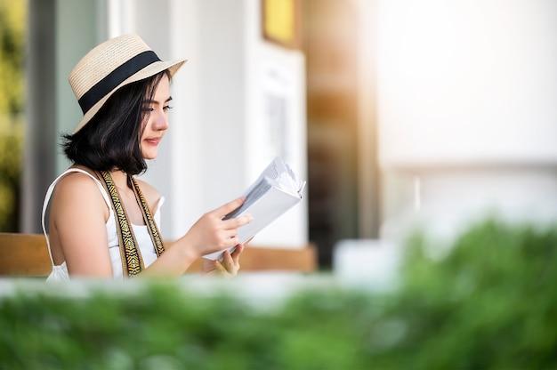Portret van jonge aziatische vrouw die hoed en vrijetijdskledingslezingsboek dragen terwijl het zitten bij het park.