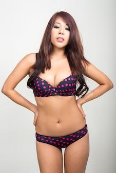 Portret van jonge aziatische vrouw die lingerie draagt tegen witte muur