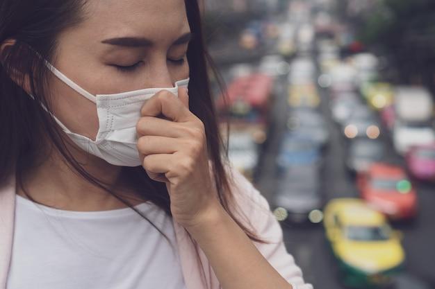 Portret van jonge aziatische vrouw die medisch gezichtsmasker in de stadsstraat draagt.