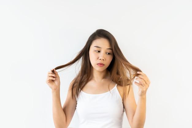 Portret van jonge aziatische vrouw die met geknoeid donkerbruin haar op witte muur wordt gefrustreerd. detailopname.