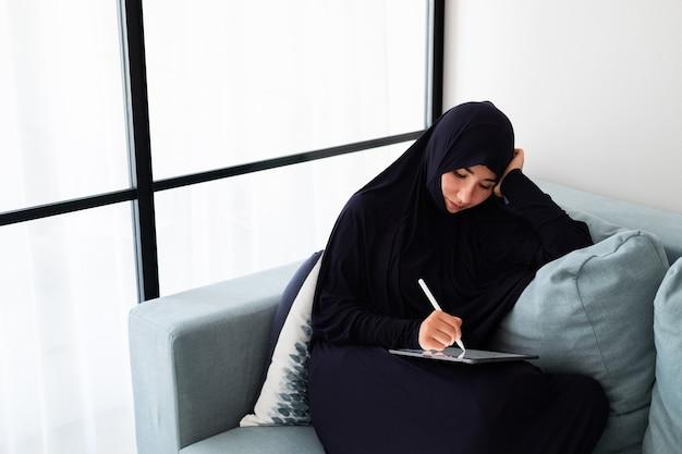 Portret van jonge aziatische vrouw die met tablet werkt