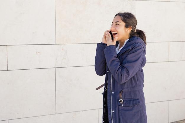 Portret van jonge aziatische vrouw die op mobiele telefoon in openlucht roddelen