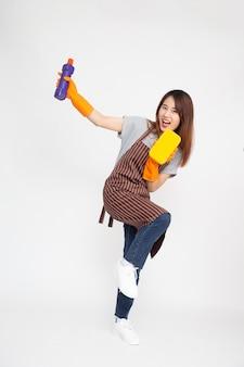 Portret van jonge aziatische vrouw die oranje rubberhandschoenen voor handenbescherming draagt