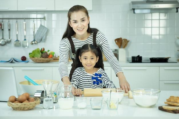 Portret van jonge aziatische vrouw en dochter bakken en koken in de keuken, activiteit van familie op schoolvakantie.