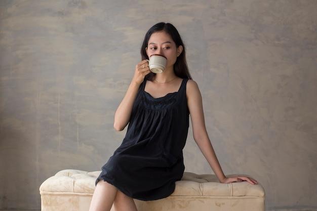 Portret van jonge aziatische vrouw koffie drinken en ontspannen op de bank