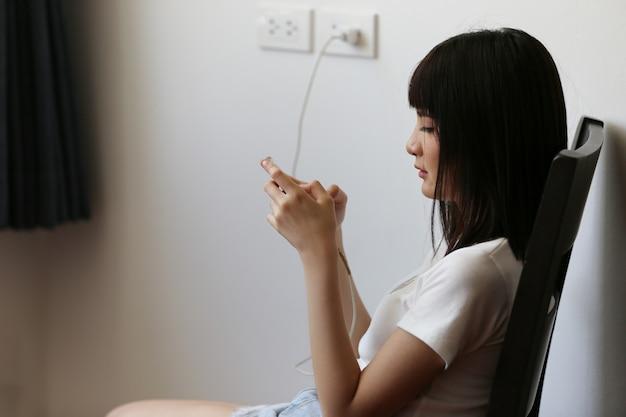 Portret van jonge aziatische vrouw lachend op mobiele telefoon chat