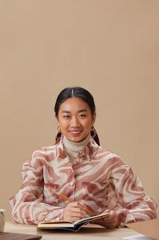 Portret van jonge aziatische vrouw lachend vooraan zittend aan tafel en schrijven in notitieblok