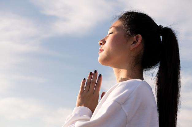 Portret van jonge aziatische vrouw mediteren bij zonsondergang