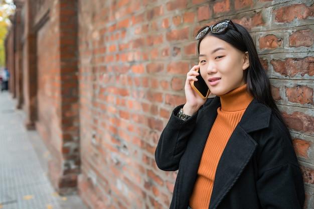Portret van jonge aziatische vrouw met behulp van haar mobiele telefoon in de straat.