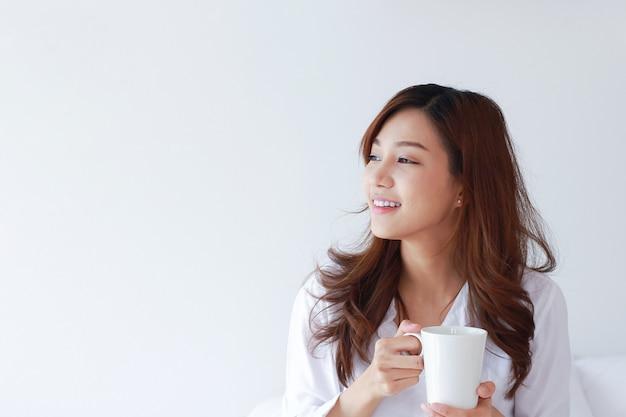 Portret van jonge aziatische vrouw met een koffiekopje op een witte muur.