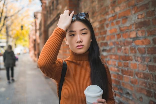 Portret van jonge aziatische vrouw met een kopje koffie terwijl ze buiten op straat staat.